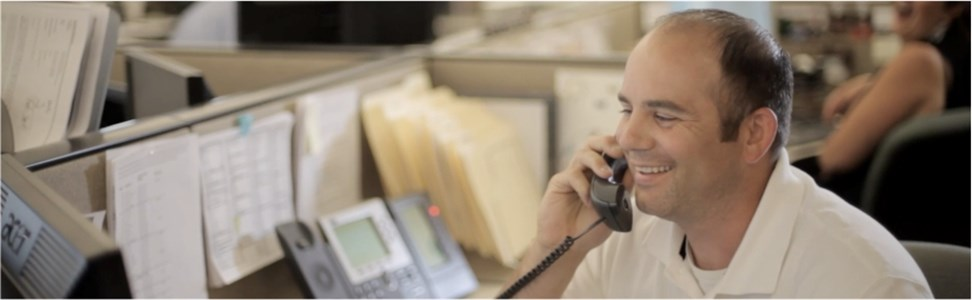Man in office answering phones